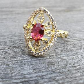 Smuk forgyldt ring med rød sten. Fåes i Str 54/ str M (3 styk tilbage) Fragt 25 kr GLS  Betaling MobilePay Se flere spændene ting under profilen.