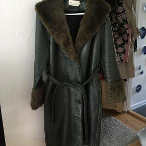 Grøn frakke købt på Nelly. Frakken er i skinnende materiale med syntetisk pels i kraven og ærmerne. Lukkes med 3 knapper og har en bindebånd i taljen.