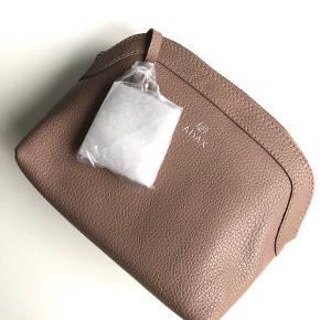 Adax lille lysebrun kosmetik taske med sølv lynlås foroven. Indeni er der et stort rum samt to lommer i hver side. Den ene lomme er med lynlås. Bagpå er der Adax logo med lille søl mønt 🐿   Tasken kan bruges som clutch eller kosmetik taske. Der er ingen stropper på den.   Byd gerne kan enten afhentes i Århus C eller sendes på købers regning 📮✉️