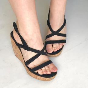 Højhælede sandaler fra Ganni, med blødt sort ruskind og kilehæl i kork. Hælen er 10 cm og foran 2 cm. Standen er god, aldrig brugt. Str. 38 og normal i pasform.