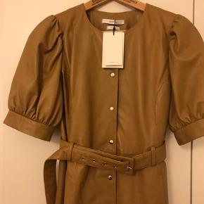 Smuk kjole i 100 procent skind fra mærket Gestuz sælges. Kjolen er en str 38 og i en mørkere beige nuance. Den går til læggen og lukkes med knapper og bindebånd. Den har korte -lidt pufærmeagtige -ærmer og rund hals. Kjolen er helt ny med prismærke. Nypris 3999kr Nupris 2500