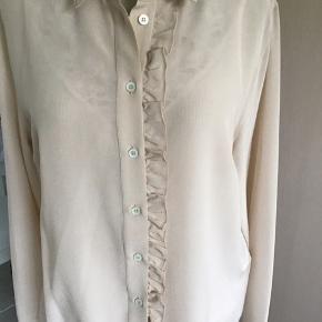 Ualmindelig smuk skjorte med flæs ned af front i den smukkeste pudder farve.. 100% Silke.. Nypris 3.000,- Bytter ikke!