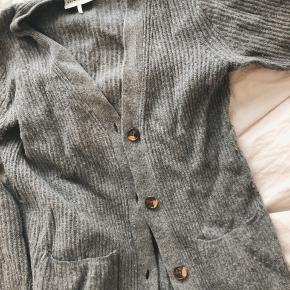 Gannicardigan i 60% uld. Har fnuller, men kan formentlig fjernes med fnugfjerner :)  Der står XS i mærket, men kan sagtens passes af en S