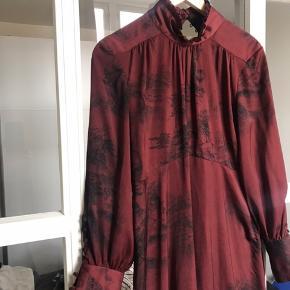 Fineste vinrøde kjole med print. Der står large i kjolen men den svarer ikke til en large. Jeg er selv en 36-38.