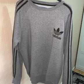 Adidas originals grå sweater i Medium. Fik den som gave, men har sjældent haft den på, da det ikke er min stil. Ved ik helt hvad en koster ny, så jeg sætter den til 200kr. Du er villig til at byde