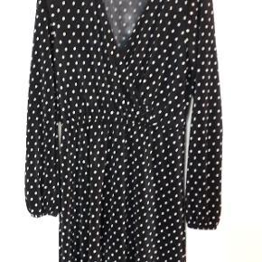 Smuk mørkeblå/næsten sort kjole med hvide prikker. Kjolen har mindre brugsspor som lidt fnuller omkring taljeelastikken, men ikke noget man tydeligt ser, kan dog fjernes med fnugfjerner. :)
