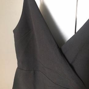 Fin sort top med dyb udskæring foran og bagpå og slids i siderne
