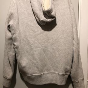 Der er ingen fejl eller skader på sweateren. Vasket få gange.  Skal blot stryges og så er den fin igen.  Den har en hoodie og lynlås.