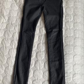 Coated Skinny Fit Jeans i sort fra VILA i str. XS.  Læder-look-a-like bukser med stretch.  Lidt mærker efter brug på numsen (forsøgt vist på billedet)