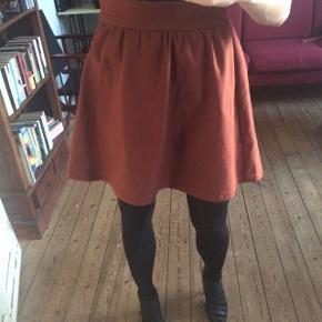 Rustfarvet, orange-brun kvalitets nederdel købt i Japan.  Lækkert, tykt stof med lidt elastik i taljen bagtil og diskret lynlås og to knapper i siden.   Lille i størrelsen.