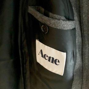 Varm og elegant, mørkegrå uldfrakke fra Acne Studios A/W09.   De indvendige trykknapper trænger til en kærlig hånd, og der er et lille hul i det indvendige fór ved ryggen – ellers fejler uldfrakken intet.  Byd endelig! ✨