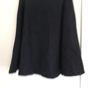 Højtaljet nederdel i uld med foer indeni. Meget fint nålestribet mønster.