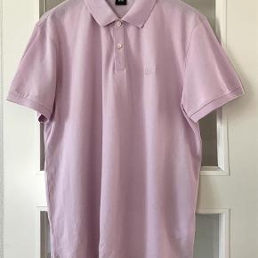 Varetype: Polo T-Shirt  Helt ubrugt Farve: Lyserød Oprindelig købspris: 600 kr.  Helt ny og ubrugt Hugo Boss polo . 100 % bomuld (prima cotton ) . Slids i siden . Måler 59 cm x 2 fra ærmegab til ærmegab 72 cm lang  Sender med DAO  Bytter ikke