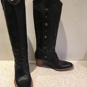 Varetype: Lange støvler Farve: Sort Oprindelig købspris: 1899 kr.  Skønne støvler i blødt skind. Rigtig pæn stand uden særlige brugsspor. Næsten ingen slid på hæl. Se billeder. Uden lynlås. Hæl ca 6,5 cm Højde målt fra fod 36 cm Omkreds ved læggen 35 cm ***Betaling kan ske med mobilepay eller TS + 5% sælgergebyr. Den angivne fragtpris er med DAO***