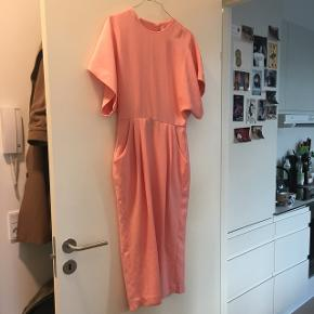 Smuk rosa/lyserød kjole fra &Other Stories, der desværre er en forkert størrelse, hvorfor den ny søger en ny ejerinde. Str. 34/S. Meget velholdt med stramsiddende talje, lukket hals og ved lænden, mens den har den smukkeste åbne ryg.