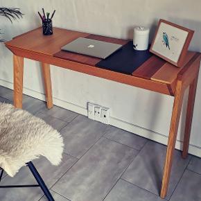 Smukt skrivebord fra Bolia: Arbor Desk, designet af Outofstock. Materiale: Finér, eg, valnød, røget eg, bøg, teak. Stel: Massiv Eg Passer perfekt til computerbord og fylder ikke meget. Der er opbevaringsrum under hver klap. Har lidt brugsspor, som vist på billede 2.    Np: 7599 kr H: 74 cm, B: 119 cm, D: 45 cm. Kommer fra et røgfrit hjem