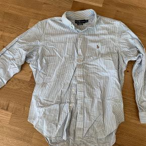 Lyseblå / hvid stribet skjorte af mærket Ralph Lauren, Custom Fit i str. US Size 16 1/2. Skjorten er aldrig brugt.. Fragt er som udgangspunkt ikke inkluderet i prisen.  Jeg har lige nu et stort udvalg af tøj til salg. Hvis du er interesseret i at købe flere ting fra mig, så er jeg åben for at lave en god deal.