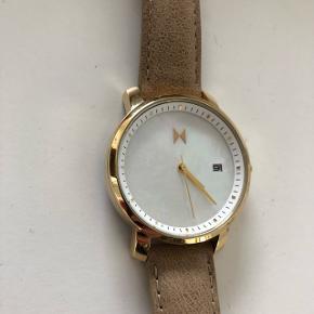 Sælger dette lækre MVMT ur med brun læderrem og perlemorsskive.  Køber betaler porto. Kan alternativt hentes og prøves på min adresse i KBH S. Tæt på Amagerbro metro st.  Tryk på billederne for at se uret bedre.  Se også min profil og alle mine mange andre flotte og billige varer jeg har til salg. ⚡️  Batteri skal udskiftes.  Perlemor - guld detaljer - brun læder - armbåndsur