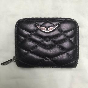 Lille sort læderpung fra zadig & voltaire. Pungen er brugt, men i rigtig god stand. Det eneste slid den har er lidt på englevingerne.