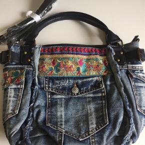 Varetype: Desigual taske Størrelse: OZ Farve: Denim  Super din taske i denim med palietter og broderi.  3 lommer med knap og 1 med lynlås udvendig.  Indvendig er der 2 lynlås rum og et uden.  Der følger lang skulderrem med.  Bytter ikke