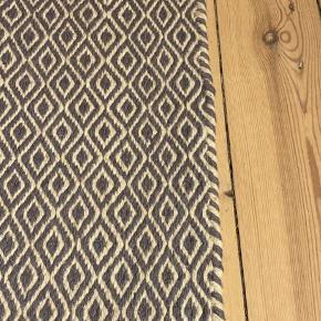 Fint gulvtæppe købt på Ellos i Marts måned til 1799kr.  Grå/blåligt/hvidt mønster. Uld  140x200cm  Sælges da det ikke passer til ny sofa.   Afhentes i Valby, sendes ikke
