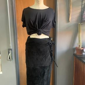 100% suede wrap skirt. Some Photos make it seem as if there is discoloration but it's just the camera and suede material combo, the color of the skirt is even and luxurious!