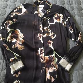 Lækker skjorte/bluse i fin kvalitet. Brugt max 5 gange, er som ny uden pletter eller skader. Bindebånd medfølger.  Ny pris 1999 kr.
