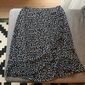 Sort og hvid prikket nederdel med flæser  Prisen er inkl. levering. Hvis der afhentes i Valby trækkes 38 kr fra 😊