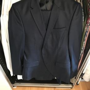"""Navyblåt herre jakkesæt fra Selected Homme med en lettere """"shiny"""" effekt. Jakkesættet er str 46 og fitter somewhere mellem str 46 og 48.  Sættet er brugt få gange, men fremstår som nyt, og har lige været forbi renseriet.   Kommer som sæt, dvs. Blazer og bukser."""