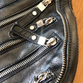 Taske i sort skind med mange lynlås detaljer.  Tasken er blevet brugt en del og metallet ved lynlåsringene bære tydeligvis præg af slid, og en læder strop mangler.  Ingen huller og indeni er den også pæn.  Sælges billigt.