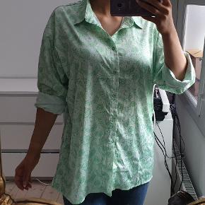 Lysegrøn og hvid skjorte med flot mønster Stoffet er glat i det Den er oversized, str 36, så den passer også 38 og evt 40.  Jeg er 171cm høj Jeg har brugt den en gang, hvor den var bundet op, da jeg synes den blev lidt for lang - men kan bæres på begge måder. Den fremtår flot og næsten som ny  Den sælges for 150kr Kan sendes med DAO for 38kr