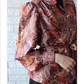 Endnu et vintage fund fra 1970 i perfekt stand. Silkeskjorter med en masse varme farver og motiver med et matchende bælte. Skjorten har nogle flotte poset ærmer, og har endnu en skøn detalje med puf i ærmerne. Matcher alt! Kun fantasien sætter grænser. Kan bruges til hverdag og fest. Passer størrelse: 32-38. Skriv en privat besked for mere info🌸