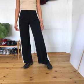 Højtaljede bukser, hvid/gul stribe i hver side. Elastisk i taljen. Str. XS