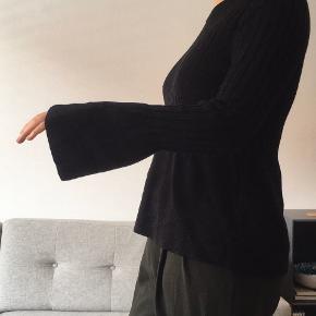 Den fine strik i 50% merino uld er fra Designers Remix X Charlotte Eskildsen.   Trøjen fremstår uden huller eller andre skader/misfarvninger.   Merinoulden gør at den ikke kradser, men er blød og varm - helt perfekt til den kommende vinter! Ærmerne har en fin vidde og snittet på trøjen giver en super fin talje.