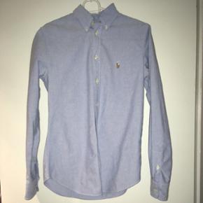 Ralph Lauren custom fit skjorte. Lille hul på ryggen. Brugt meget lidt. Kan hentes i Nørresundby eller sendes med DAO på købers regning.