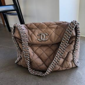 Overvejer at sælge min lækre Chanel taske, da jeg ikke synes jeg får den brugt nok. Den er købt i en vintage-designershop i New York, ingen tvivl om ægthed. Farven er sådan grå-beige, taupe hedder den vist.  Røg- og lugtfri. Nyrenset og imprægneret ved salg.  Måler 32 x 23 når den er lukket, hanken er 60 cm og sidder så godt på skulderen.  Prisen er 10.000kr. Bytter ikke.