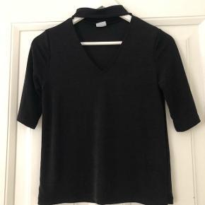 Gina Tricot T-shirt med bånd omkring halsen. Kvaliteten er glat og skinnende.