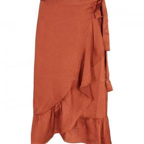Nej Noir Mika slå-om nederdel i rustfarve i super god stand, kun brugt få gange. Kan afhentes i Valby. Ved forsendelse betaler køber porto.