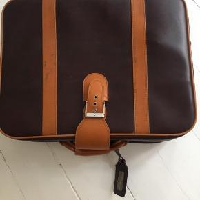 Fin retro vinyl kuffert i fin varm brunlige farver. God lynlås/lås. Mål: 55x45cm og 15 dyb. God stand. God til opbevaring samtidig med den ser hyggelig ud.