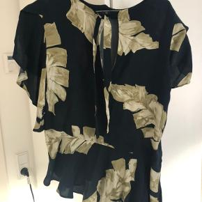 Super fin asymmetrisk bluse med flotte detaljer. Blusen er længere i den ene side end den anden, hvilket giver en flot effekt. Lukkes i rykken med bindebånd og har fine detaljer på ærmerne.