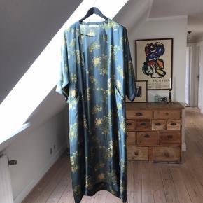 Super smuk kimono i 100% silke. Bundfarven er blålig, og blomsterne grønlige og gyldne. Brugt ganske få gange!  Nyprisen var 3000,- Jeg har fået fjernet en løbegang hvor bæltet sad fast på ryggen. Der er ikke noget der ses med mindre man går meget tæt på. Har forsøgt at fotografere det.  Handler gerne via mobilepay