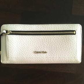Hvid Calvin Klein Clutch i PU.  Aldrig brugt. Lynlåsen i siden er lidt stram, men selve pungen er aldrig brugt.