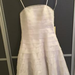 Smuk ny konfirmationskjole. Str XS. Helt ny og stadig med mærket på. Nypris kr 2299.  Kjolen er virkelig smuk og har et enkelt klassisk snit. Meget feminint. Lukkes i ryggen med lynlås. Sidder flot på kroppen.