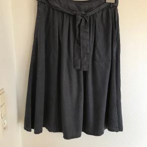 Blød og meget behagelig mørkeblå nederdel fra det italienske mærke Marie Sixtine. To dybe lommer foran og lynlås i venstre side.  Stoffet er tencel ( bæredygtigt naturmateriale fremstillet af træflis). Stoffet er temperatur regulerende og fugtabsorberende. Kan vaskes og bibeholder sin blødhed. Længde: 67 cm, livvidde 76 cm.