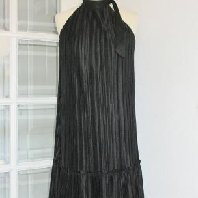 Sød plisséret sort kjole som er plisséret i hele kjolens længde. Fast halskant med sløjfe. Kjolen har en 20 cm bred flæse forneden. Materialet er polyester  Beystvidde: Flexibel Længde: 95 cm  Ingen byt, og prisen er fast