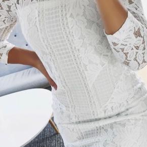 Neo Noir konfirmationskjole i off-white blonde med 7/8 lange ærmer.  Lukkes i ryggen med lynlås og en enkel knap i nakken.  Helt ny og ubrugt med mærke og extra knap.  Størrelsen er xs  Omkreds bryst 86 cm. Længde 81 cm.  Nypris 700 kr.