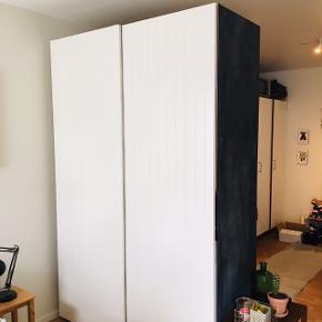 PAX skab fra IKEA med skydelåger og garderobelys sælges ifm. flytning. Nypris var omkring 5000-6000 kr. med alt inklusiv. Den ene side på skabet er malet med tavlemaling, og på bagsiden er der blevet monteret en hvidmalet MDF-plade (som kan fjernes), da skabet er blevet brugt som rumdeler. Skabet indeholder to bøjlestænger, to netskuffer, to udtrækkelig skohylder og fire hylder.   Mål: 145 (B) x 225 (H) x 60 (D)