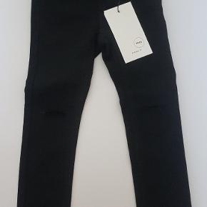 Fitting skinny denim i sort. Hul på knæene (som er meningen) og sorte sten på højre baglomme.