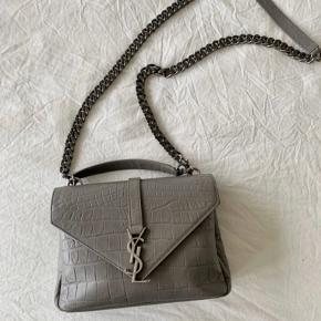 """Saint Laurent Medium College taske i """"Grey Crocodile embossed leather"""". Tasken er købt secondhand, kvittering haves ikke men alt andet medfølger inkl autenticitetskort.   Jeg får desværre ikke brugt den nok og derfor sælges den. Det eneste slid er lidt på kæden og i hjørnerne. Mp: 7000"""