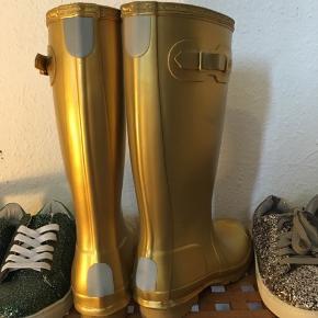 Vildt flotte gummistøvler i skinnende guld. Limited edition fra Hunter. Ikke bred i skaftet. Aldrig brugt, men den ene har et par mærker i gummiet. Bytter ikke.